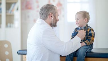 Doktor hört Herzschlag eines Kindes ab