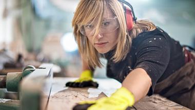 Weibliche Schreinerin arbeitet an einem Möbestück